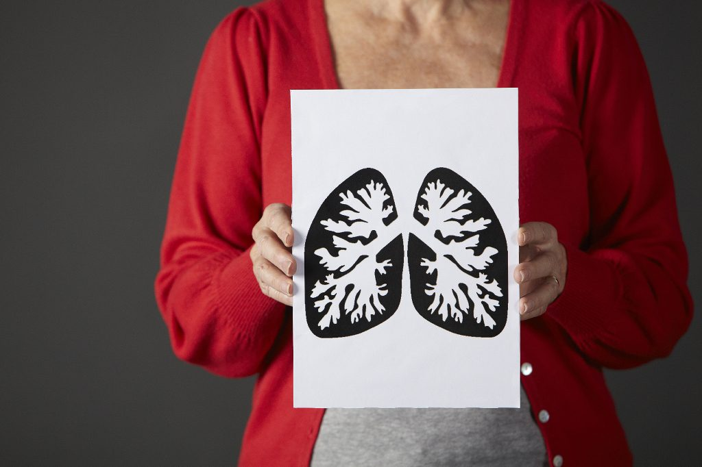 Older woman hold a drawing of lungs up to her chest.