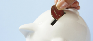 Photo of a hand putting a coin in a white piggy bank