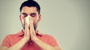 Man sneezing from pollutants in air